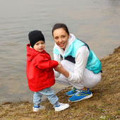 Beautiful young family having fun near the river — ストック写真