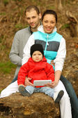 Young family sitting on a large tree and uses the tablet — Stock Photo