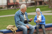 Grandfather and grandson eating — Stock Photo