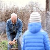 Nipote sembra suo nonno dividere la legna da ardere — Foto Stock