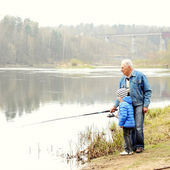 Grandfather and grandson are fishing — Stock Photo