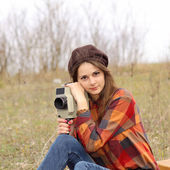 Hipster girl in a plaid shirt makes movies — Stock Photo