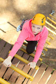 Beautiful girl climber climbs up the stairs — Stock Photo