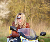 Biker girl with sunglasses sitting on motorcycle — Stock Photo