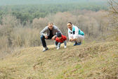 Beautiful young sporty family stands back on the mountain — Photo