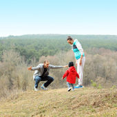 Beautiful young sporty family stands back on the mountain — Foto de Stock