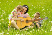 Family playing guitar — Stockfoto