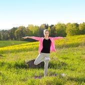 Woman practices yoga — Stock Photo