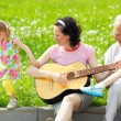 Mother playing guitar for her children — Stock Photo #50366899