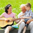 Mother playing guitar for her children — Stock Photo #50366901