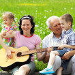 Mother playing guitar for her children — Stock Photo #50366905