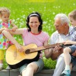Mother playing guitar for her children — Stock Photo #50366923