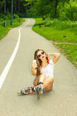 Girl on roller skates sitting on the road — Stock Photo