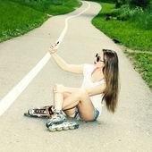 Mädchen auf rollschuhen sitzt auf der straße — Stockfoto