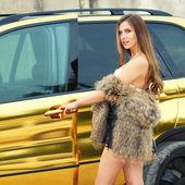 Ragazza in bikini vicino auto d'oro — Foto Stock