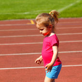 Little girl running at the stadium — Stock Photo