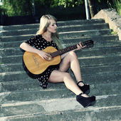 Girl sitting on stairs with guitar — Stock Photo