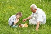 Grand-père et petit-fils, jouant aux échecs — Photo
