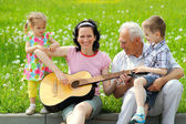 Mother playing guitar for her children — Stock Photo