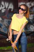 Funky girl posing with skateboard — Stock Photo