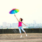 Girl with umbrella on roof — Stock Photo