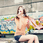 Hipster girl blows bubbles — Stock Photo