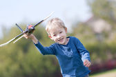 Child playing with a plane — Stock Photo