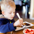 Child eating breakfast — Stock Photo