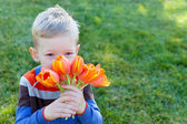 Boy holding flowers — Stock Photo