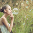 Girl starts soap bubbles — Stock Photo