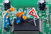 Miniature engineers fixing error on chip — Stock Photo