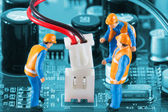 Miniature engineers fixing wire connector — Stock Photo