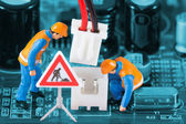 Miniature engineers fixing wire connector — Photo