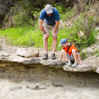 Father and son looking at fossilized dinosaur footprints. Dinosa - Stock Photo