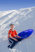 Boy with a sledge on the slope of snow-white dunes of gypsum san — Stock Photo