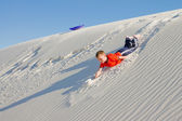 The boy rolled down the slope of snow-white dunes of gypsum sand — Stock Photo