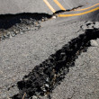 Cracks in the road, destroying the road surface - Stock Photo