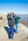 Two children on a mountain top looking through binoculars on a n — Stock Photo
