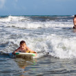 Stock Photo: Joyful child on board is racing with wave. Bodyboarding