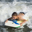 Stock Photo: Bodyboarding. Child slides on short board on soft wave