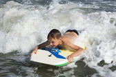 Bodyboarding. Child slides on a short board on a soft wave — Stock Photo