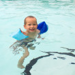 Stock Photo: Little boy learning to swim in the pool in multicolored arm ruff
