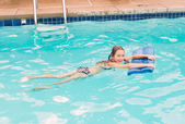 Girl trained to swim in the pool with the help of the board — Stock Photo