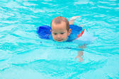 A little boy swimming in the pool in multicolored arm ruffles — Stock Photo