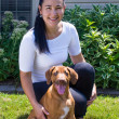 Стоковое фото: The black-haired woman with a two-month Rhodesian ridgeback