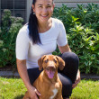 The black-haired woman with a two-month Rhodesian ridgeback — 图库照片