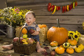 Cheerful kid with a pumpkin and apple — Stock Photo