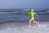Happy kid runs along the sea — Stock Photo