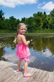 Girl is fishing in the pond — Stock Photo
