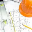 Safety orange helmet and level on project drawings — Stock Photo